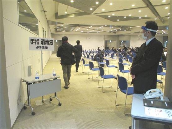 【写真:受講者の椅子の間隔が広く斜めに並んでいる講演会場】